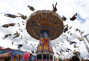 People enjoy a fairground ride during the opening day at 180th Oktoberfest in Munich September 21, 2013. Millions of beer drinkers from around the world will come to the Bavarian capital over the next two weeks for the 180th Oktoberfest, which starts today and runs until October 6. REUTERS/Michael Dalder (GERMANY - Tags: ENTERTAINMENT SOCIETY)